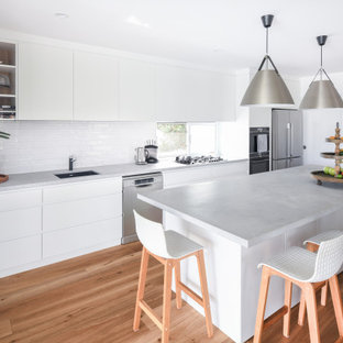 Photo of a mid-sized contemporary single-wall open plan kitchen in Sydney with an undermount sink, flat-panel cabinets, white cabinets, quartz benchtops, white splashback, ceramic splashback, stainless steel appliances, medium hardwood floors, with island, brown floor and grey benchtop.