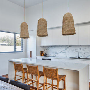 Photo of a beach style galley open plan kitchen in Gold Coast - Tweed with a drop-in sink, flat-panel cabinets, white cabinets, grey splashback, stainless steel appliances, dark hardwood floors, with island, brown floor and grey benchtop.