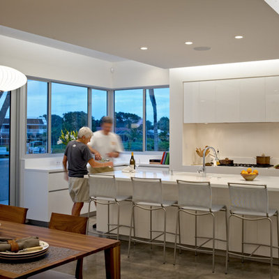 Minimalist eat-in kitchen photo in Other with flat-panel cabinets, white cabinets and white backsplash