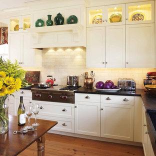 Diseño de cocina tradicional con armarios estilo shaker, puertas de armario blancas, salpicadero beige, salpicadero de azulejos tipo metro, electrodomésticos de acero inoxidable y encimera de esteatita