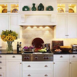 Diseño de cocina tradicional con armarios estilo shaker, puertas de armario blancas, salpicadero beige, electrodomésticos de acero inoxidable, encimera de esteatita y salpicadero de piedra caliza