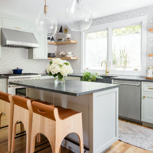 This is an example of a mid-sized transitional l-shaped separate kitchen in San Francisco with an undermount sink, shaker cabinets, beige cabinets, granite benchtops, multi-coloured splashback, subway tile splashback, stainless steel appliances, medium hardwood floors, with island, black benchtop and brown floor.