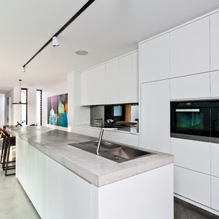 Photo of a contemporary open plan kitchen in Perth with a double-bowl sink, flat-panel cabinets, white cabinets, concrete benchtops, mirror splashback, black appliances, concrete floors, with island and grey floor.