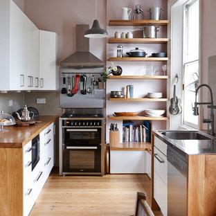 Kleine Moderne Küche ohne Insel mit flächenbündigen Schrankfronten, weißen Schränken, Arbeitsplatte aus Holz, Küchenrückwand in Grau, Rückwand aus Porzellanfliesen, braunem Holzboden und schwarzen Elektrogeräten in London