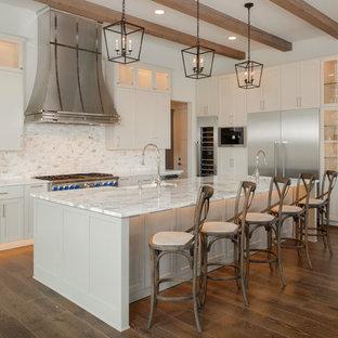 Große Klassische Wohnküche in L-Form mit Landhausspüle, Glasfronten, weißen Schränken, bunter Rückwand, Küchengeräten aus Edelstahl, braunem Holzboden, Kücheninsel, Rückwand aus Marmor, Marmor-Arbeitsplatte, weißer Arbeitsplatte und braunem Boden in Austin