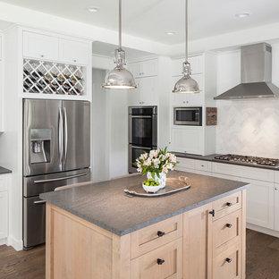 Elegant medium tone wood floor kitchen photo in Austin with shaker cabinets, white cabinets, soapstone countertops, multicolored backsplash, subway tile backsplash, stainless steel appliances and an island