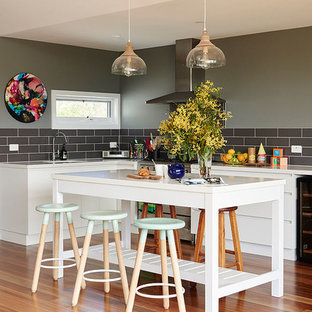 Large transitional l-shaped open plan kitchen in Melbourne with an undermount sink, white cabinets, quartz benchtops, ceramic splashback, stainless steel appliances, with island, orange floor, flat-panel cabinets, black splashback and medium hardwood floors.