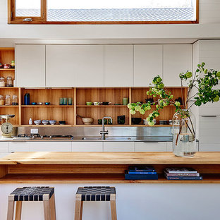 Inspiration for a beach style kitchen in Geelong with an integrated sink, open cabinets, light wood cabinets, stainless steel benchtops, metallic splashback and with island.