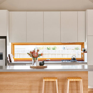 Photo of a beach style kitchen in Geelong with flat-panel cabinets, white cabinets, window splashback, stainless steel appliances, light hardwood floors, with island, beige floor and grey benchtop.