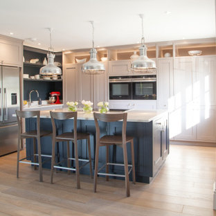 Inspiration for a classic l-shaped kitchen in Surrey with a submerged sink, shaker cabinets, quartz worktops, stainless steel appliances, light hardwood flooring, an island, grey cabinets and beige floors.