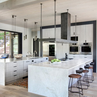 This is an example of a country u-shaped kitchen in Other with an undermount sink, flat-panel cabinets, stainless steel appliances, light hardwood floors, multiple islands, grey cabinets, beige floor and grey benchtop.