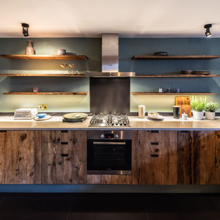 This is an example of a medium sized contemporary l-shaped kitchen in London with flat-panel cabinets, light wood cabinets, quartz worktops, blue splashback, stainless steel appliances and black floors.