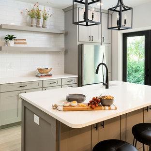 Offene, Einzeilige, Große Klassische Küche mit Landhausspüle, Schrankfronten im Shaker-Stil, grauen Schränken, Quarzwerkstein-Arbeitsplatte, Küchenrückwand in Weiß, Rückwand aus Keramikfliesen, Küchengeräten aus Edelstahl, hellem Holzboden, Kücheninsel, gelbem Boden und weißer Arbeitsplatte