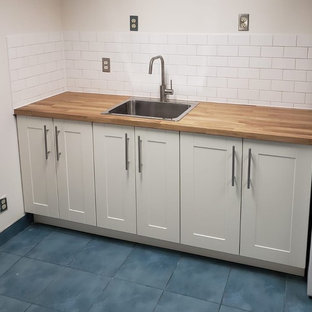 Design ideas for a small scandinavian single-wall kitchen in Toronto with a drop-in sink, shaker cabinets, white cabinets, wood benchtops, white splashback, subway tile splashback, white appliances, porcelain floors, no island, blue floor and brown benchtop.