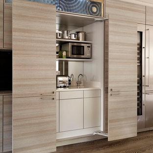 Moderne Küche mit flächenbündigen Schrankfronten, hellen Holzschränken, Küchengeräten aus Edelstahl, dunklem Holzboden und Rückwand aus Spiegelfliesen in London
