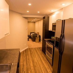 他の地域の小さいコンテンポラリースタイルのおしゃれなキッチン (ダブルシンク、フラットパネル扉のキャビネット、淡色木目調キャビネット、コンクリートカウンター、白いキッチンパネル、セラミックタイルのキッチンパネル、シルバーの調理設備の、クッションフロア、茶色い床) の写真