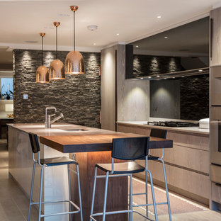 Contemporary galley kitchen in Berkshire with a submerged sink, flat-panel cabinets, grey cabinets, stainless steel appliances, an island and grey floors.