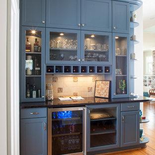 Medium sized traditional kitchen in Detroit with recessed-panel cabinets, beige splashback, medium hardwood flooring, ceramic splashback, stainless steel appliances, brown floors, blue cabinets and black worktops.