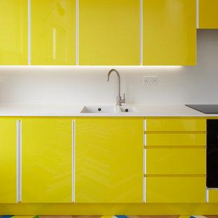 ロンドンのコンテンポラリースタイルのおしゃれなキッチン (ダブルシンク、フラットパネル扉のキャビネット、黄色いキャビネット、白いキッチンパネル、塗装フローリング、マルチカラーの床) の写真