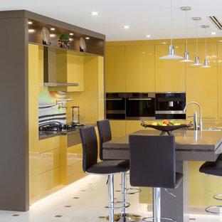 パースのモダンスタイルのおしゃれなキッチン (フラットパネル扉のキャビネット、黄色いキャビネット、御影石カウンター、マルチカラーのキッチンパネル、ガラス板のキッチンパネル、シルバーの調理設備、茶色いキッチンカウンター) の写真
