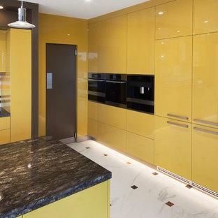 パースのモダンスタイルのおしゃれなキッチン (フラットパネル扉のキャビネット、黄色いキャビネット、御影石カウンター、マルチカラーのキッチンパネル、ガラス板のキッチンパネル、シルバーの調理設備の、黒いキッチンカウンター) の写真