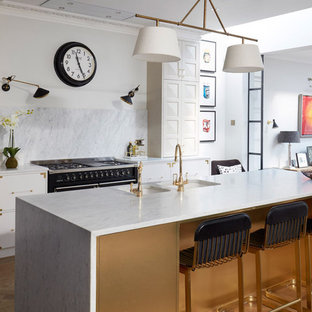 Photo of a large classic galley kitchen in London with a double-bowl sink, flat-panel cabinets, white cabinets, white splashback, stone slab splashback, black appliances, medium hardwood flooring, an island, brown floors and white worktops.