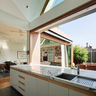Réalisation d'une très grande cuisine ouverte parallèle design avec un évier encastré, un placard à porte plane, des portes de placard blanches, un plan de travail en marbre, un électroménager en acier inoxydable et béton au sol.