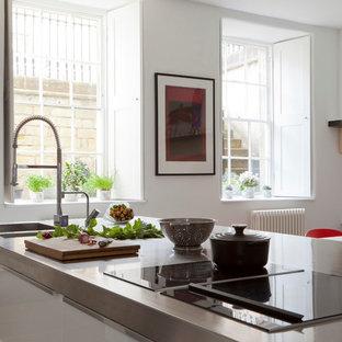 ハートフォードシャーの中サイズの地中海スタイルのおしゃれなアイランドキッチン (一体型シンク、フラットパネル扉のキャビネット、白いキャビネット、ステンレスカウンター、シルバーの調理設備の) の写真