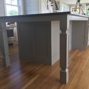 Zweizeilige, Mittelgroße Klassische Küche mit flächenbündigen Schrankfronten, Speckstein-Arbeitsplatte, Rückwand aus Holzdielen, Küchengeräten aus Edelstahl, braunem Holzboden und schwarzer Arbeitsplatte in Portland Maine