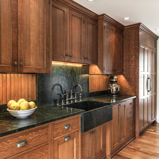 Inspiration for a mid-sized traditional l-shaped separate kitchen in Portland Maine with a farmhouse sink, recessed-panel cabinets, medium wood cabinets, soapstone benchtops, black splashback, stone slab splashback, panelled appliances, light hardwood floors and no island.