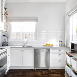 Design ideas for a transitional l-shaped kitchen in Melbourne with a double-bowl sink, shaker cabinets, white cabinets, white splashback, subway tile splashback, stainless steel appliances, dark hardwood floors, brown floor and grey benchtop.