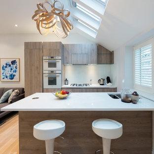 ロンドンの小さいコンテンポラリースタイルのおしゃれなキッチン (フラットパネル扉のキャビネット、珪岩カウンター、白い調理設備、淡色無垢フローリング、ベージュの床、アンダーカウンターシンク、中間色木目調キャビネット) の写真