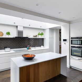 Inspiration for a contemporary l-shaped kitchen/diner in London with flat-panel cabinets, white cabinets, black splashback, stainless steel appliances, dark hardwood flooring and an island.