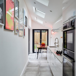 Inspiration for a small contemporary single-wall kitchen/diner in London with a submerged sink, flat-panel cabinets, white cabinets, integrated appliances, no island, grey floors and grey worktops.