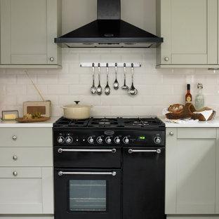 ロンドンのヴィクトリアン調のおしゃれなキッチン (シェーカースタイル扉のキャビネット、グレーのキャビネット、サブウェイタイルのキッチンパネル、黒い調理設備) の写真