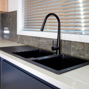 シドニーの広いコンテンポラリースタイルのおしゃれなキッチン (ドロップインシンク、フラットパネル扉のキャビネット、淡色木目調キャビネット、クオーツストーンカウンター、グレーのキッチンパネル、セラミックタイルのキッチンパネル、黒い調理設備、ラミネートの床、アイランドなし、ベージュの床、白いキッチンカウンター) の写真