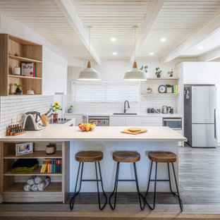 Inspiration for a contemporary u-shaped kitchen in Sydney with an undermount sink, flat-panel cabinets, white cabinets, white splashback, stainless steel appliances, dark hardwood floors, a peninsula, brown floor, white benchtop and exposed beam.