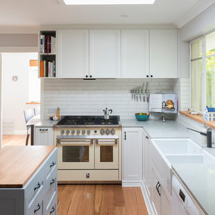 Inspiration for a transitional l-shaped separate kitchen in Canberra - Queanbeyan with a farmhouse sink, shaker cabinets, white cabinets, white splashback, brick splashback, white appliances, medium hardwood floors, with island, brown floor and grey benchtop.