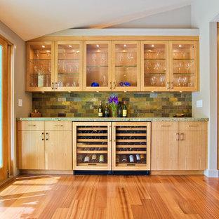 Пример оригинального дизайна интерьера: параллельная кухня-гостиная среднего размера в стиле модернизм с стеклянными фасадами, фасадами цвета дерева среднего тона, паркетным полом среднего тона, фартуком из сланца, столешницей из гранита, зеленым фартуком, техникой под мебельный фасад, коричневым полом и зеленой столешницей без острова