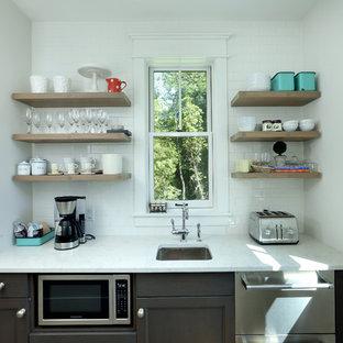 他の地域の小さいカントリー風おしゃれなキッチン (落し込みパネル扉のキャビネット、濃色木目調キャビネット、アイランドなし、アンダーカウンターシンク、白いキッチンパネル、サブウェイタイルのキッチンパネル、パネルと同色の調理設備、淡色無垢フローリング、茶色い床、クオーツストーンカウンター、白いキッチンカウンター) の写真