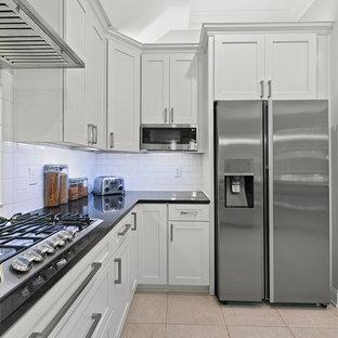 ジャクソンビルの中サイズのモダンスタイルのおしゃれなキッチン (エプロンフロントシンク、シェーカースタイル扉のキャビネット、白いキャビネット、御影石カウンター、白いキッチンパネル、サブウェイタイルのキッチンパネル、シルバーの調理設備の、セラミックタイルの床、ベージュの床、黒いキッチンカウンター) の写真