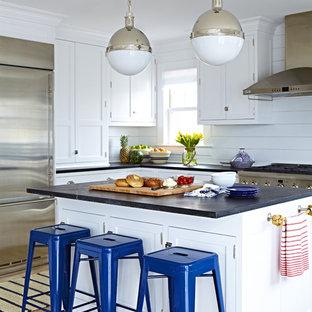 ニューヨークの中くらいのビーチスタイルのおしゃれなキッチン (エプロンフロントシンク、シェーカースタイル扉のキャビネット、白いキャビネット、ソープストーンカウンター、白いキッチンパネル、シルバーの調理設備、淡色無垢フローリング、塗装板のキッチンパネル) の写真
