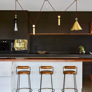 This is an example of a large contemporary galley kitchen in Brisbane with flat-panel cabinets, dark wood cabinets, black splashback, black appliances, with island, black benchtop and grey floor.