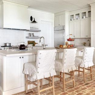Exempel på ett shabby chic-inspirerat kök, med skåp i shakerstil, vita skåp, vitt stänkskydd, rostfria vitvaror, tegelgolv, en köksö, rött golv och bänkskiva i betong