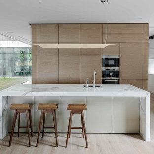 Photo of a modern galley open plan kitchen in Sydney with an undermount sink, glass-front cabinets, light wood cabinets, window splashback, panelled appliances, light hardwood floors, with island, beige floor and white benchtop.