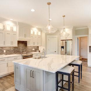 他の地域の広いトランジショナルスタイルのおしゃれなキッチン (落し込みパネル扉のキャビネット、黄色いキャビネット、シルバーの調理設備、無垢フローリング、ダブルシンク、大理石カウンター、茶色いキッチンパネル、モザイクタイルのキッチンパネル、茶色い床) の写真