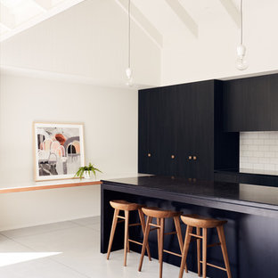 Photo of a contemporary galley kitchen in Melbourne with flat-panel cabinets, black cabinets, white splashback, subway tile splashback, with island, white floor and black benchtop.