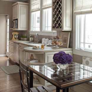 Elegant eat-in kitchen photo in San Francisco with raised-panel cabinets, beige cabinets and beige backsplash