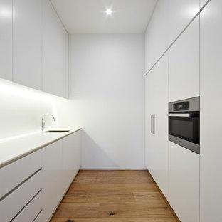 Foto de cocina de galera, nórdica, pequeña, cerrada, con armarios con paneles lisos, puertas de armario blancas, electrodomésticos con paneles y suelo de madera clara