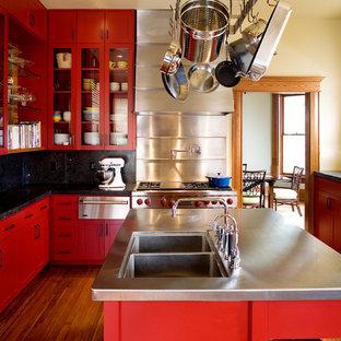 オースティンのトランジショナルスタイルのおしゃれなキッチン (ダブルシンク、ガラス扉のキャビネット、赤いキャビネット、ステンレスカウンター、黒いキッチンパネル、シルバーの調理設備の、無垢フローリング) の写真